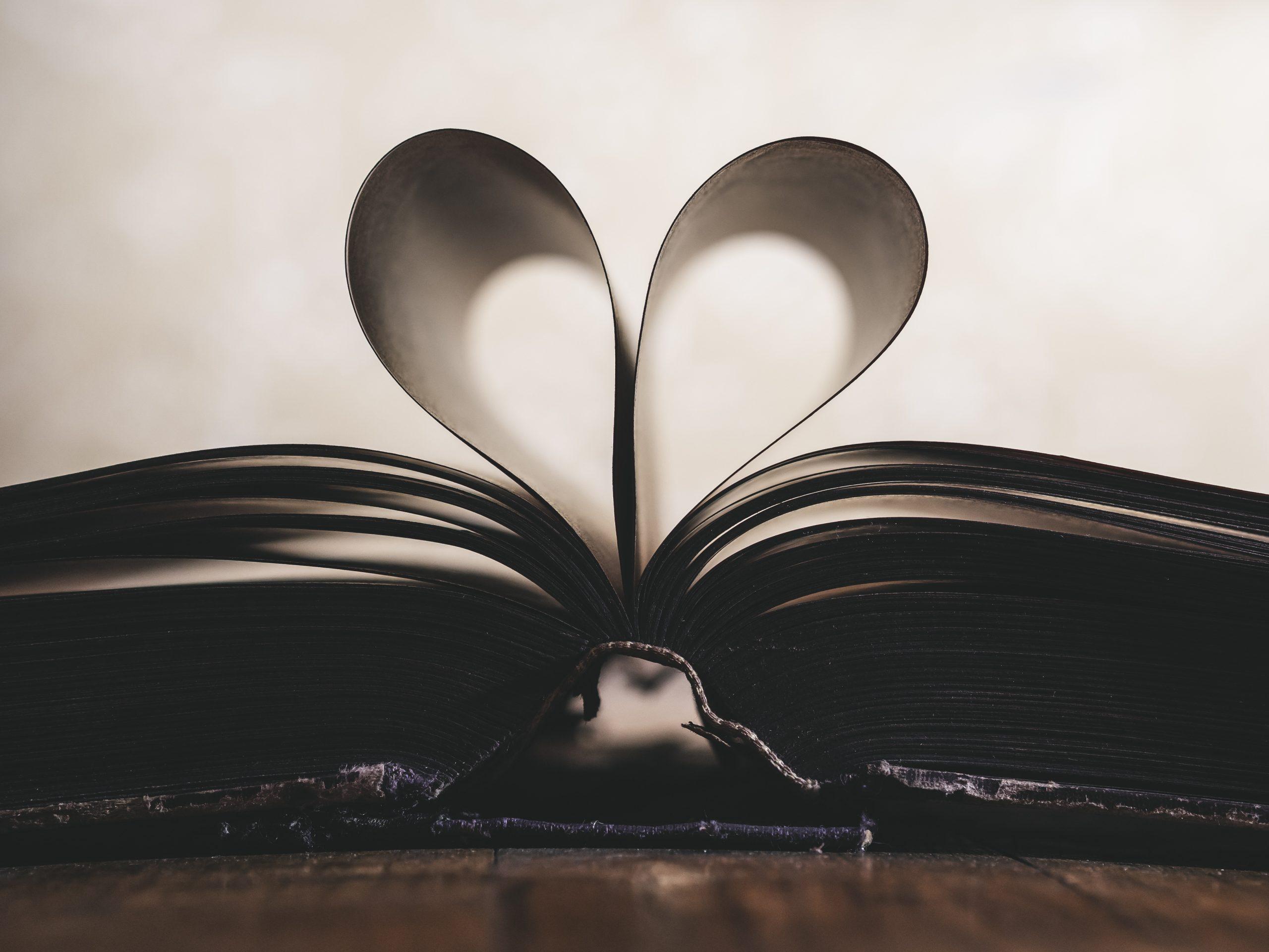 Ein Buch liegt offen auf einem Tisch, man sieht es im Profil. Zwei Seiten bliden ein Herz.