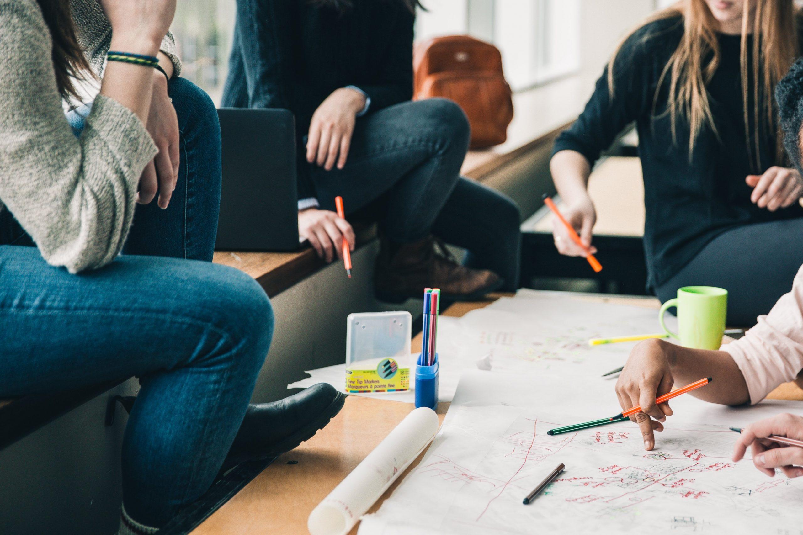 Man sieht einen Tisch mit Arbeitsmaterial, eine Gruppe junger Menschen sitzt am Tisch und unterhält sich.